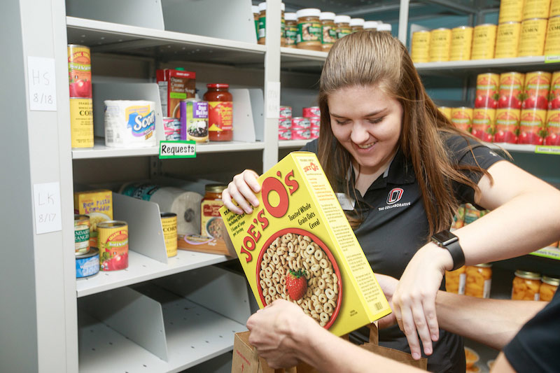 A student grabs items from the food pantry
