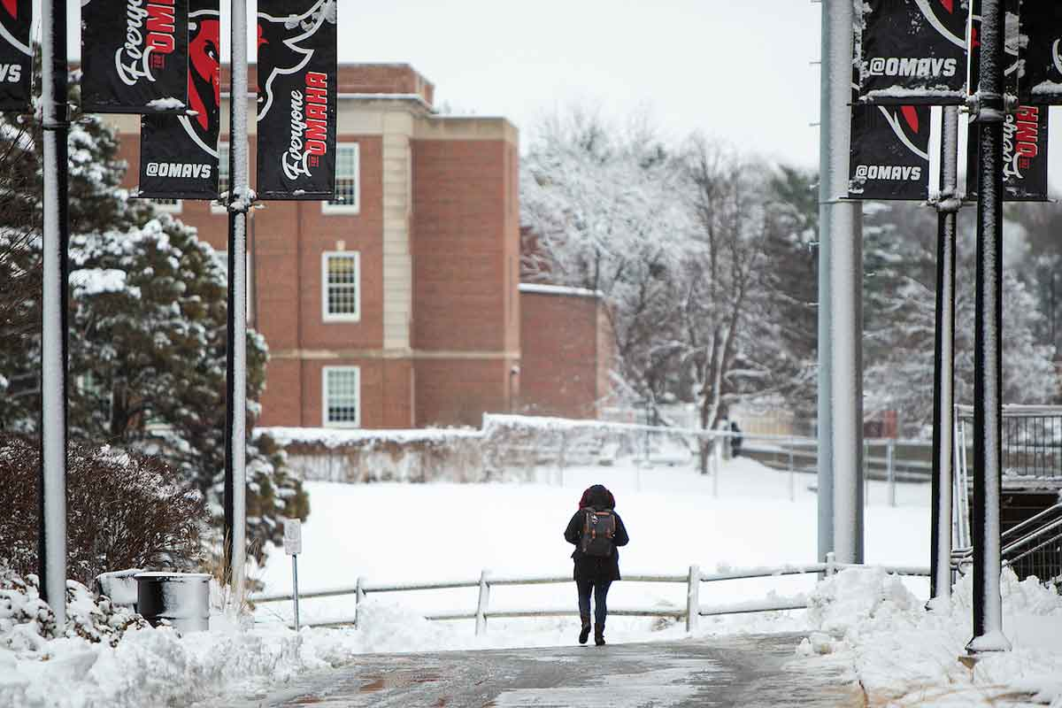 A student walks past Sapp Fieldhouse on the UNO Dodge Campus