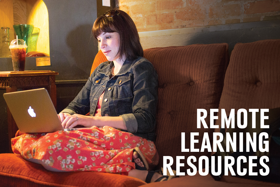 A young white brunette woman in a floral dress sits on a couch and types on her laptop.