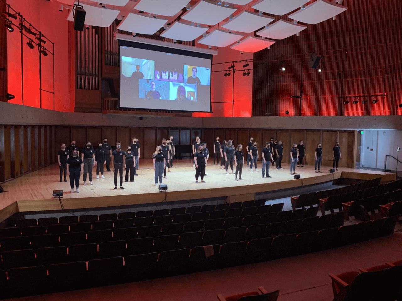 The UNO Concert Choir standing on a wooden stage with red lighting. All students are wearing jeans, black tee shirts, and masks.