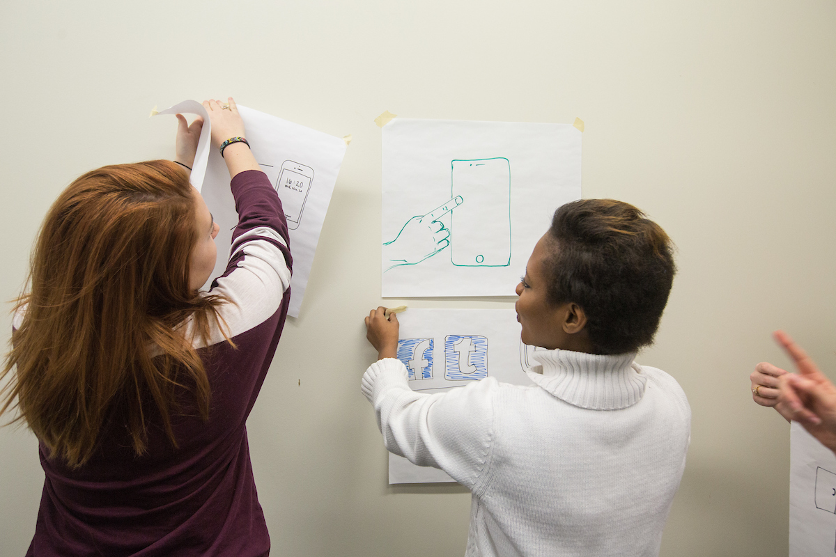 Two students working at a white board.