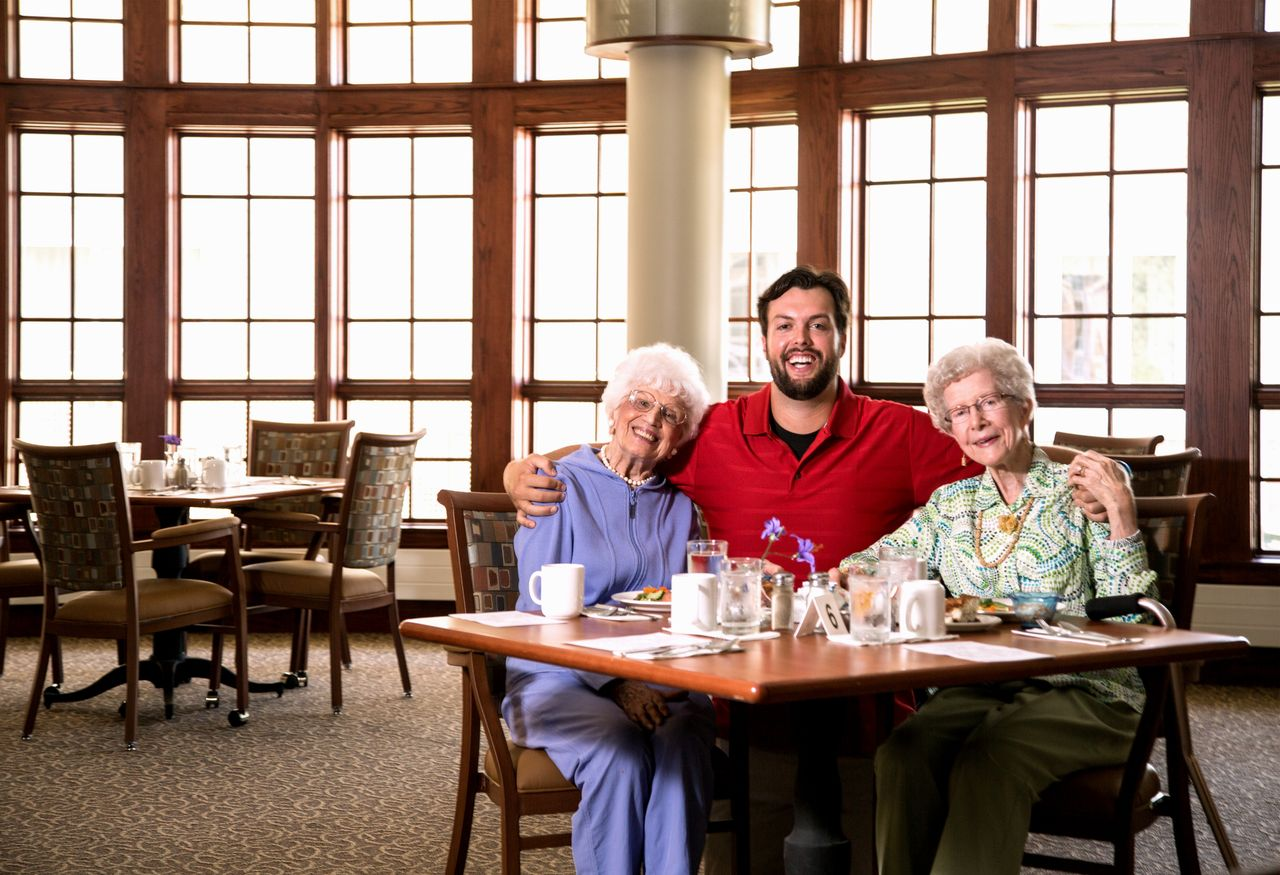 Creating living environments for a lifetime department of male student seated with two older women in dining room xflitez Choice Image