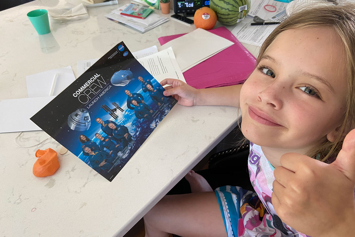 Maddie Torson, an Omaha second grader, opening her free kit for Virtual Space Camp.