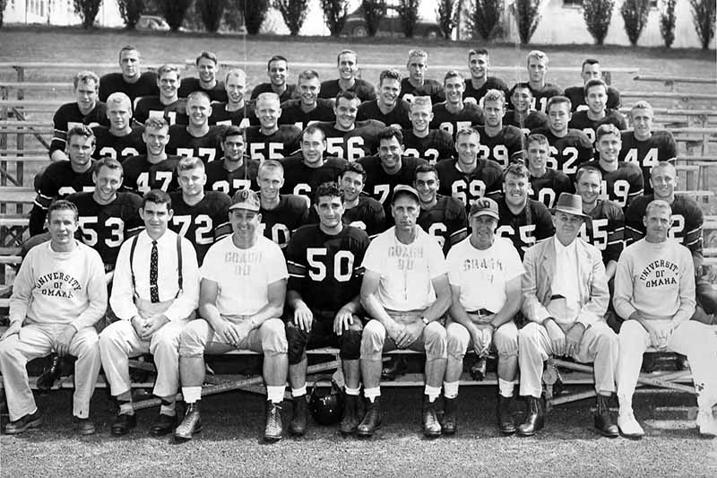 Football players and coaches seated on stadium bleachers for formal team portrait