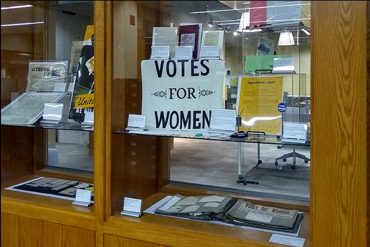 banner that says 'votes for women' within display cases