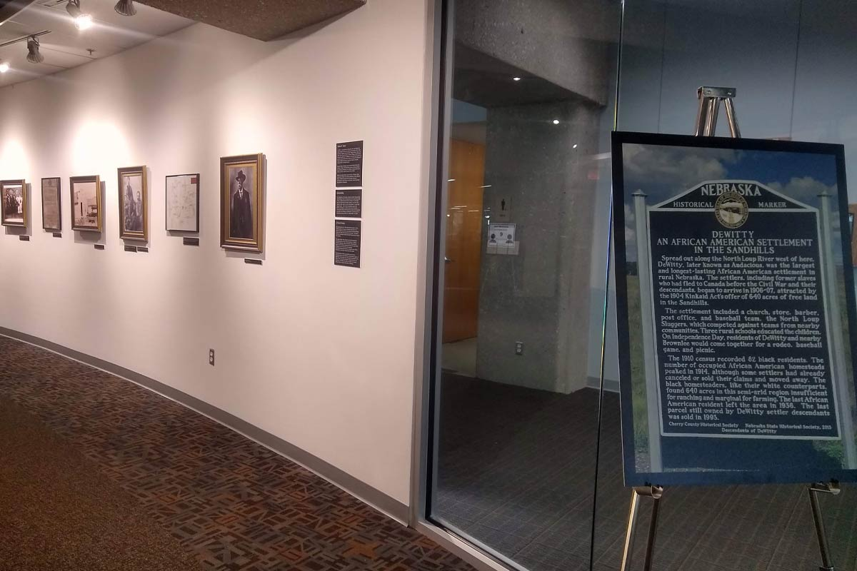 art gallery with photos on the walls and a stand and sign describing the exhibit
