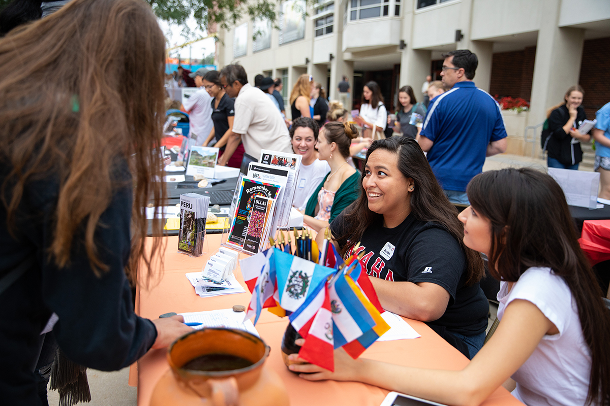 two women sit at a table at the study abroad fair, speaking with visitors to their table.
