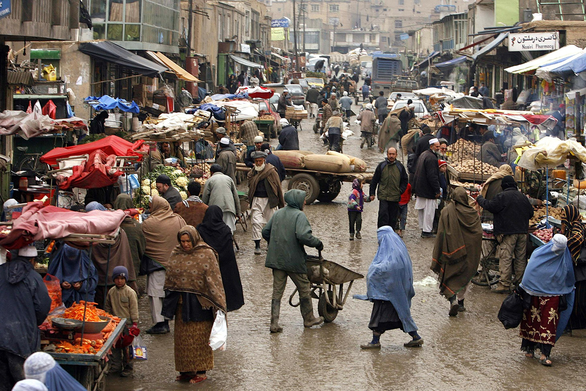 Busy market street in an Afghan town. Men women and children shop at market stalls for fruits and vegetables.