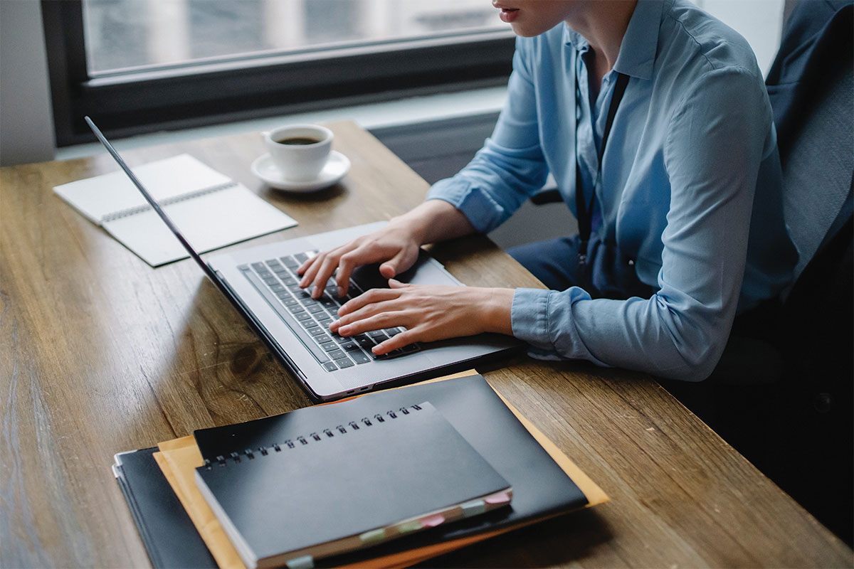 Person working on computer at desk with coffee