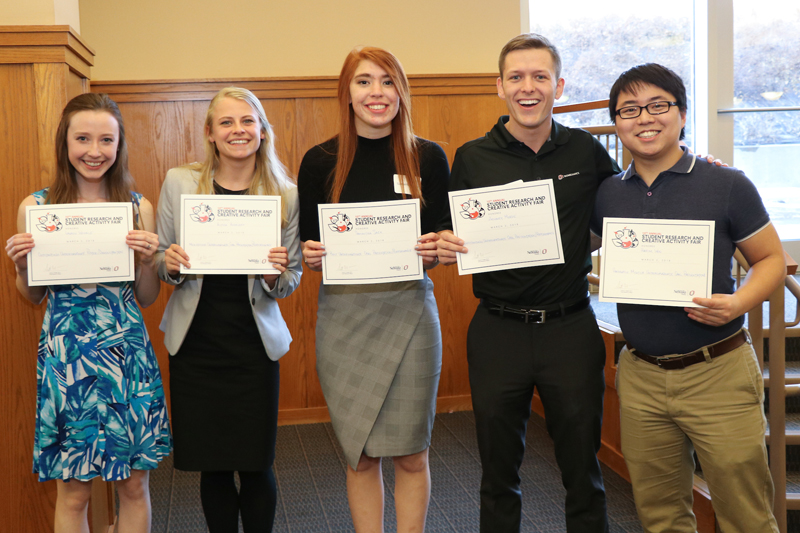 Sack (center) stands with other students recognized at the Student Research and Creative Activity Fair, including fellow Goldwater scholars Zachary Meade and Harim Won.