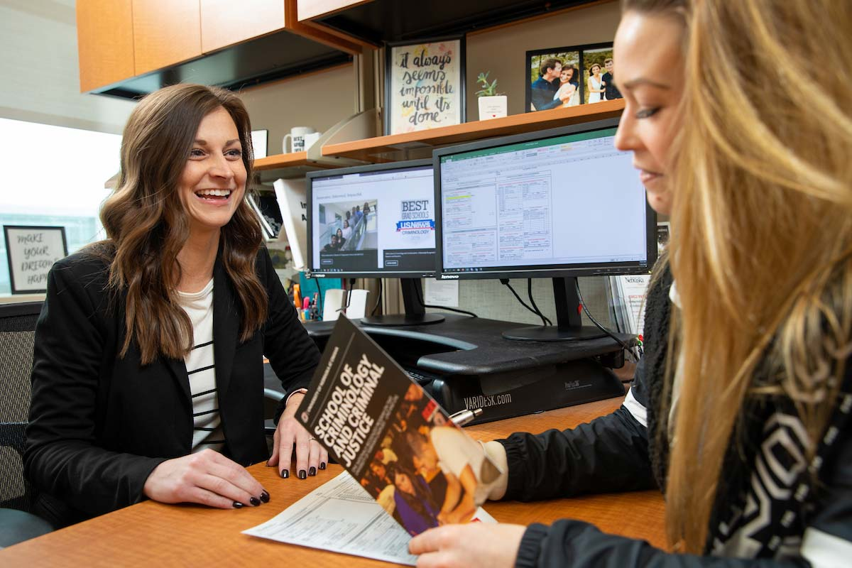 Katie Hansen, advisor for the School of Criminology and Criminal Justice, speaks with a student.
