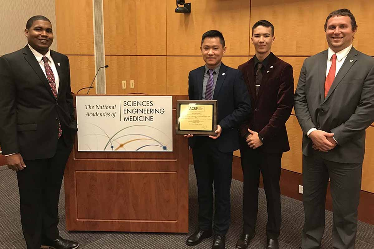 """Joseph Harris, Chenyu """"Victor"""" Huang Ph.D., Alexander Nguyen, and Christopher Kelley pose with an award from the Airport Collaborative Research Program (ACRP) next to a podium with a banner that reads """"The National Academies of Sciences, Engineering, and Medicine."""""""