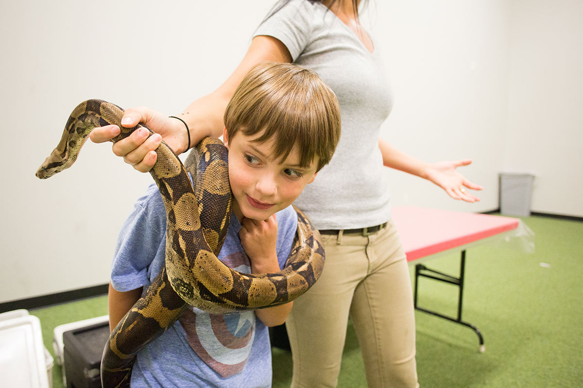 A child stands with a snake around his neck