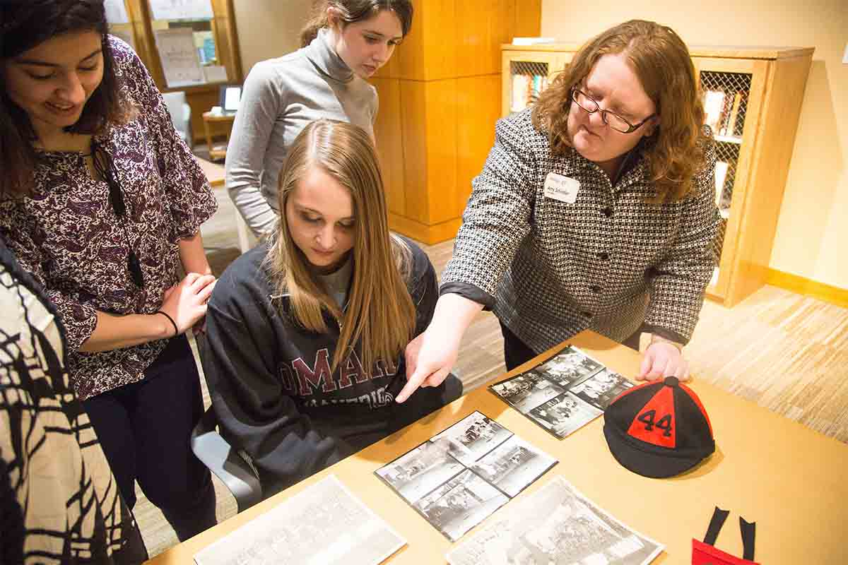 Students and UNO archivists examine materials kept within the Criss Library Archives & Special Collections