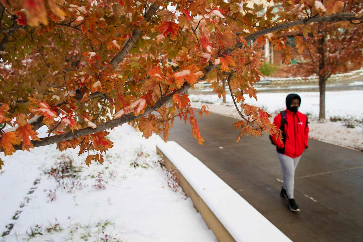 A photo of a student in a mask walking through campus with snow on the ground.